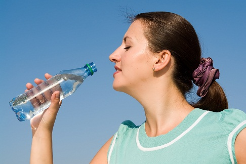 beautiful woman drinks water on a blue sky