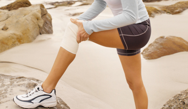 Side view of a concerned woman wearing a knee support holding her knee with her foot on a rock